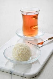 Vista ingrandita della torta di pasta biscotto al cocco e una tazza di tè su un tavolo