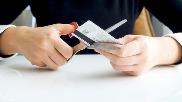 Vista del primo piano dell'impiegato di banca femminile che taglia la carta di credito di plastica.