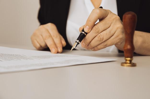 Vista del primo piano della mano femminile che tiene la penna. carta e timbro sulla scrivania.