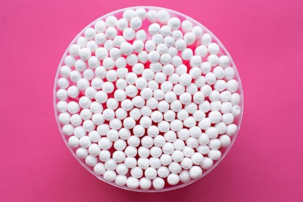 Vista ingrandita dall'alto sulla confezione rotonda di cotton fioc su sfondo rosa.