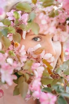 Vista ravvicinata di una ragazza con la pelle bianca e chiara attraverso la coppia di alberi di mele in fiore nel giardino concetto senza allergie e pelle perfetta