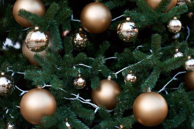 Vista del primo piano dell'albero di natale verde decorato con palline dorate e luci.