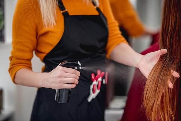 Parrucchiere di vista del primo piano che spruzza i capelli lunghi del cliente nel salone di bellezza