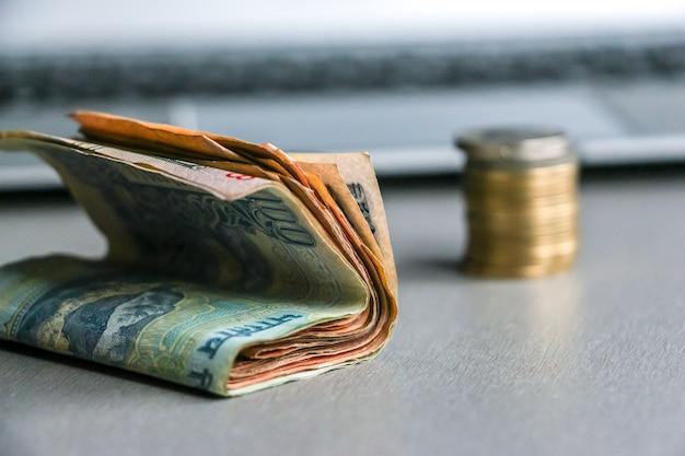 Vista ingrandita della valuta indiana (banconote e monete), tastiera del computer portatile in background.