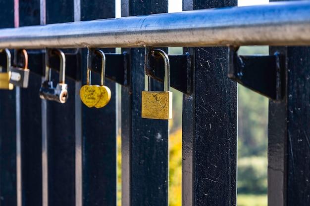 Primo piano dei lucchetti dell'amore appesi a un recinto del ponte