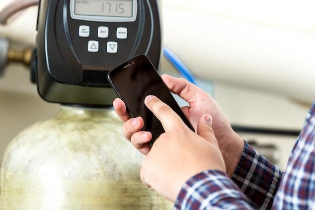 Vista del primo piano dell'uomo che digita la lettura del contatore dell'attrezzatura di fabbrica sullo smartphone