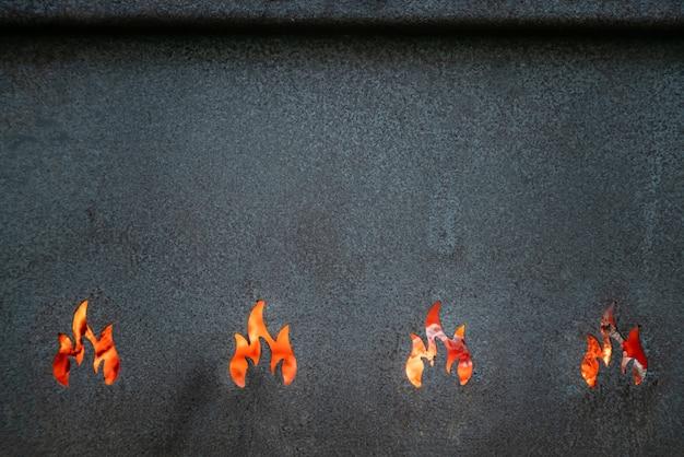 Vista ingrandita della struttura della griglia del barbecue in metallo. sfondo di fiamme roventi.