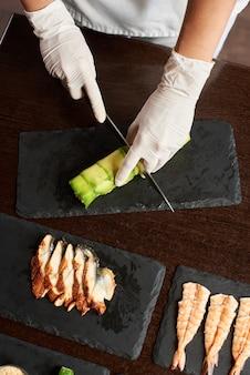 Vista del primo piano del processo di preparazione del sushi di rotolamento. lo chef sta tagliando il rotolo sulla lastra di pietra nera. vista dall'alto