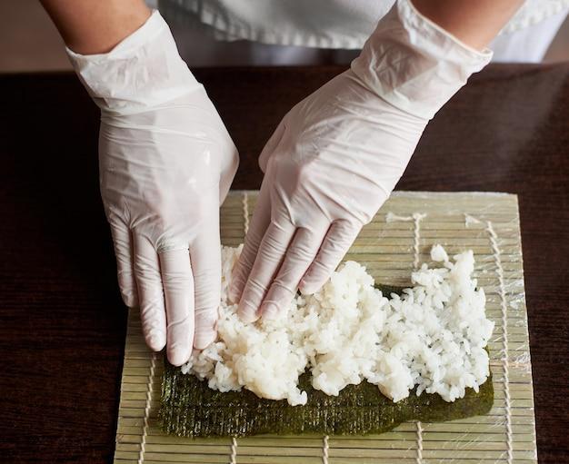 Vista ingrandita del processo di preparazione del sushi di laminazione. nori e riso bianco sulla stuoia di bambù. le mani dello chef toccano il riso. lo chef inizia a cucinare il sushi.