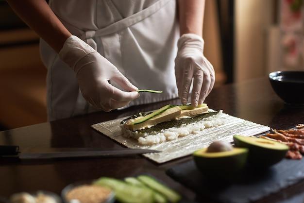 Vista del primo piano del processo di preparazione del sushi di laminazione con nori, riso, cetriolo e frittata sulla stuoia di bambù