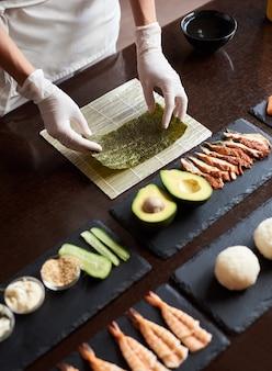 Vista ingrandita del processo di preparazione del sushi di laminazione