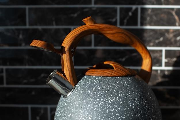 Vista del primo piano della teiera moderna in acciaio con manico in legno. foto scura.