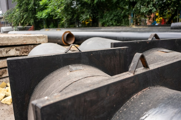 Vista ingrandita di due nuovi tubi dell'acqua isolati sulla strada della città in una giornata estiva. concetto di infrastruttura fognaria urbana, ammodernamento e ricostruzione del sistema idrico sotterraneo.