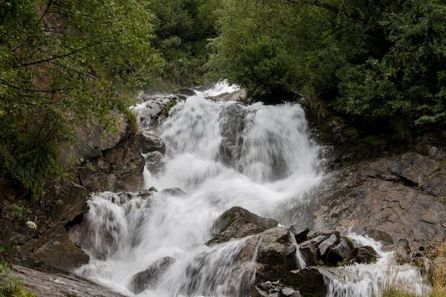 Primo piano scene cascata in montagna, parco nazionale dombai, caucaso, russia, europa. paesaggio estivo, tempo soleggiato e giornata di sole