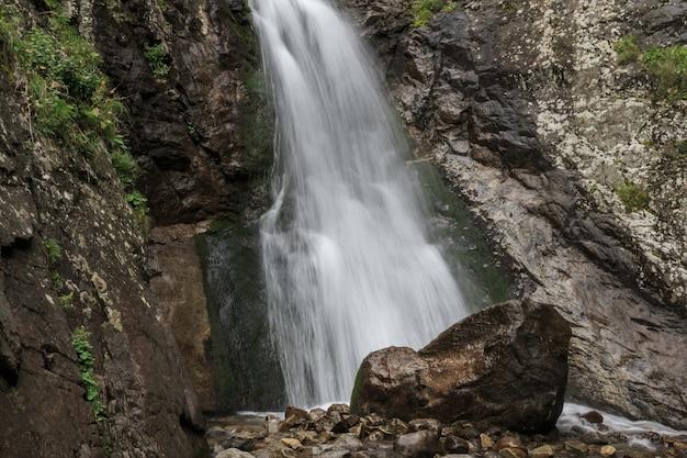 Vista del primo piano delle scene della cascata in montagne, parco nazionale dombay, caucaso, russia, europa. paesaggio estivo e giornata di sole