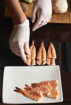 La vista del primo piano delle mani della donna nei guanti sta preparando i gamberetti per il sushi di rotolamento nel ristorante