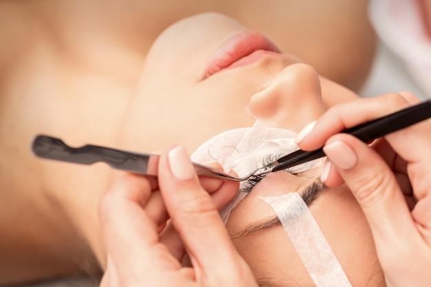Vista del primo piano di giovane donna caucasica che ha procedura di estensione delle ciglia nel salone di bellezza
