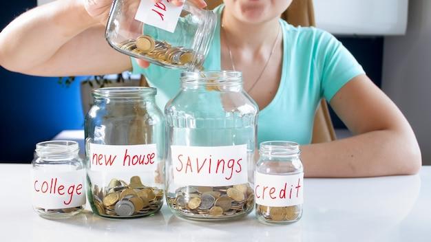 Vista del primo piano del barattolo di vetro di riempimento della giovane donna con risparmio di denaro. concetto di investimento finanziario, crescita economica e risparmio bancario.