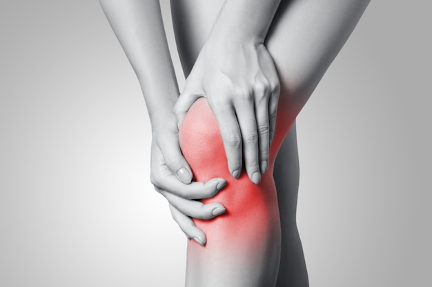 Primo piano di una giovane donna con dolore al ginocchio su sfondo grigio. foto in bianco e nero con punto rosso.