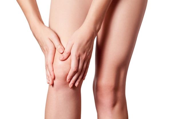 Primo piano di una giovane donna con dolore al ginocchio su sfondo bianco.