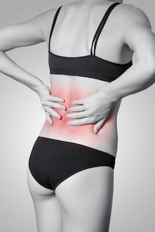 Primo piano di una giovane donna con dolore alla schiena su sfondo grigio. foto in bianco e nero con punto rosso.