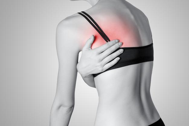 Primo piano di una giovane donna con dolore alla schiena su sfondo grigio
