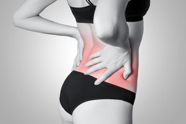 Primo piano di una giovane donna con dolore alla schiena isolato su sfondo bianco su sfondo grigio