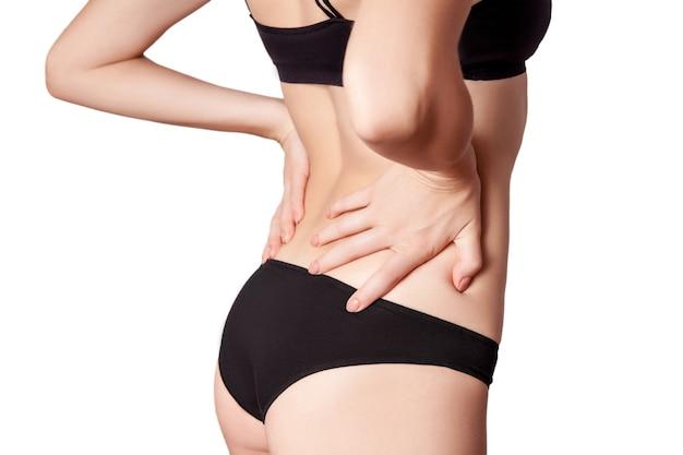 Vista del primo piano di una giovane donna con dolore alla schiena. isolato su sfondo bianco su sfondo bianco.