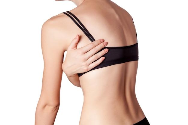 Primo piano di una giovane donna con dolore alla schiena su sfondo bianco.