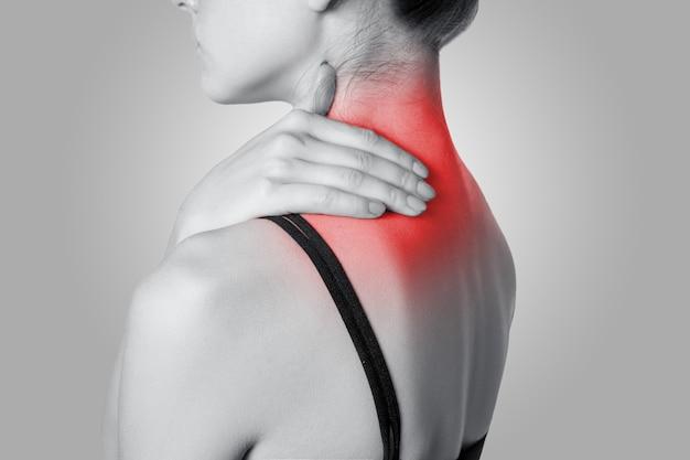 Primo piano di una giovane donna con dolore alla spalla o al collo su sfondo grigio. foto in bianco e nero con punto rosso.