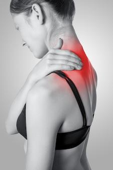 Primo piano di una giovane donna con dolore alla spalla o al collo su sfondo grigio