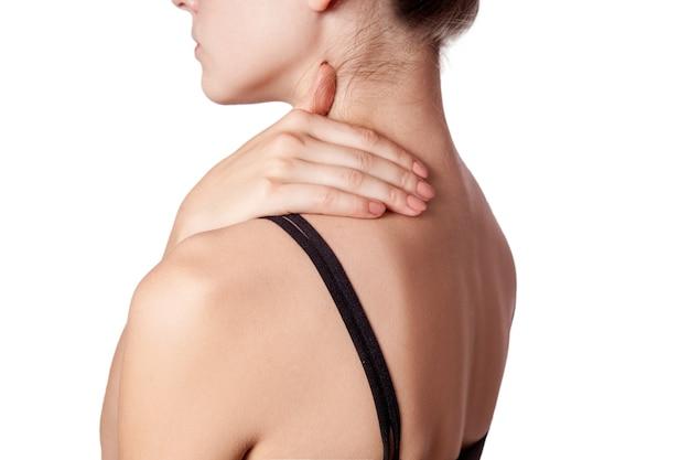 Primo piano di una giovane donna con dolore alla spalla o al collo su sfondo bianco.