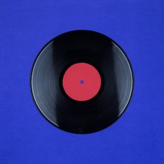 Primo piano del disco di vinile long play con etichetta con copia spazio sulla superficie blu