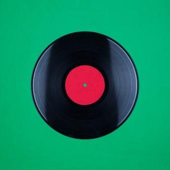 Primo piano del record del gioco lungo del vinile con l'etichetta con lo spazio della copia su superficie verde
