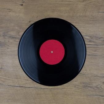 Primo piano del record del gioco lungo del vinile con l'etichetta con lo spazio della copia sulla superficie di legno