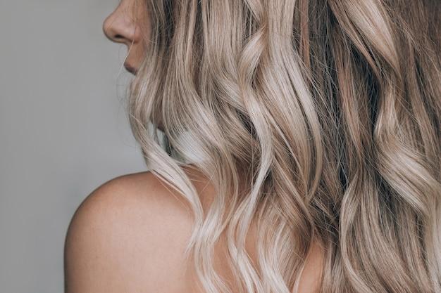 Primo piano dei capelli biondi ondulati di una giovane donna bionda su uno sfondo grigio risultato della colorazione