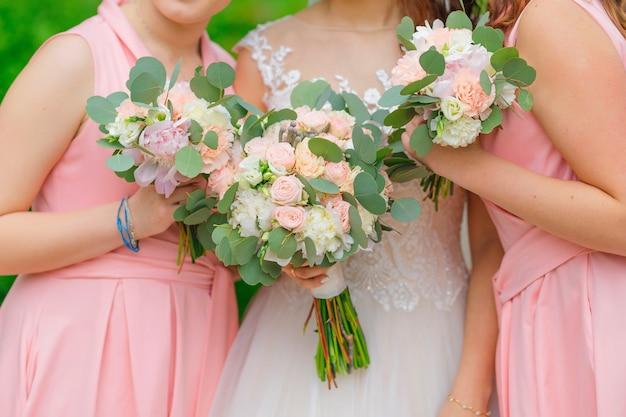 Primo piano di bouquet da sposa nelle mani della sposa e delle damigelle.