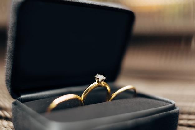 Primo piano di fedi nuziali e un anello di fidanzamento con una grande gemma in una scatola di velluto nero contro a