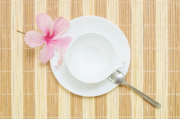 Tazza ceramica bianca del primo piano con il cucchiaio inossidabile sulla stuoia