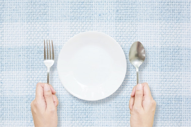 Il piatto ceramico bianco del primo piano con la forcella ed il cucchiaio inossidabili in donna passano sul fondo strutturato stuoia blu del tessuto