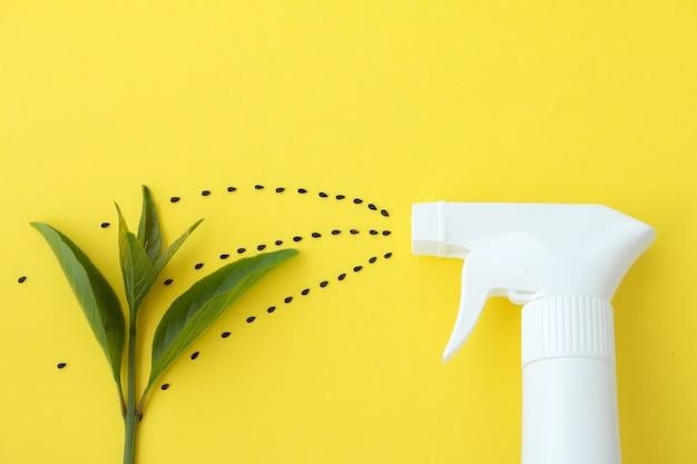 Closeup della bottiglia di spruzzo bianco su sfondo giallo con la linea di spruzzatura da semi di saseme nero alla pianta del bambino, spruzzare acqua o piantare concetto
