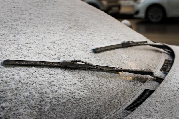 Primo piano dei tergicristalli e del parabrezza glassato dell'automobile coperti di ghiaccio e di neve. tempo invernale