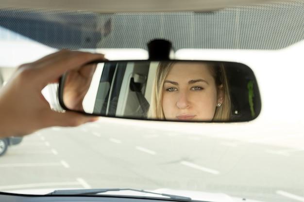 Primo piano della donna che regola lo specchietto dell'auto e guarda nel riflesso