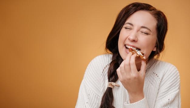 Primo piano di una donna che morde un biscotto di natale di pan di zenzero su uno sfondo giallo