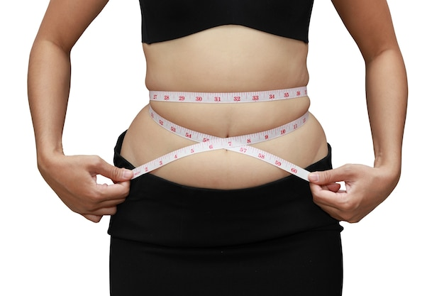 Grasso corporeo della donna del primo piano in sovrappeso dalla parete isolata e bianca dello stomaco del nastro di misura con il percorso di residuo della potatura meccanica