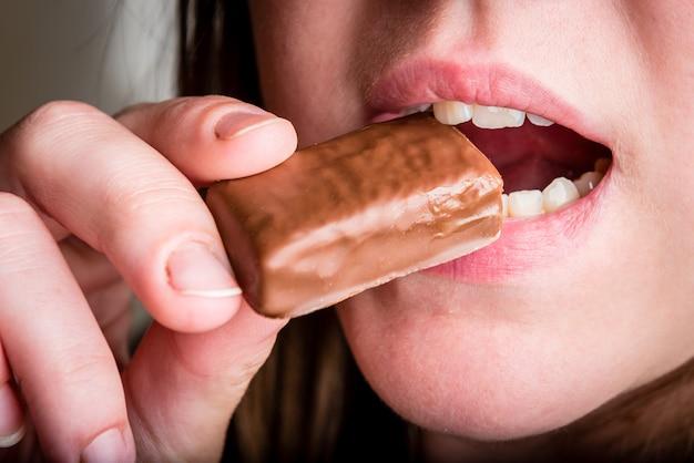 Primo piano della donna che mangia dolce al cioccolato.