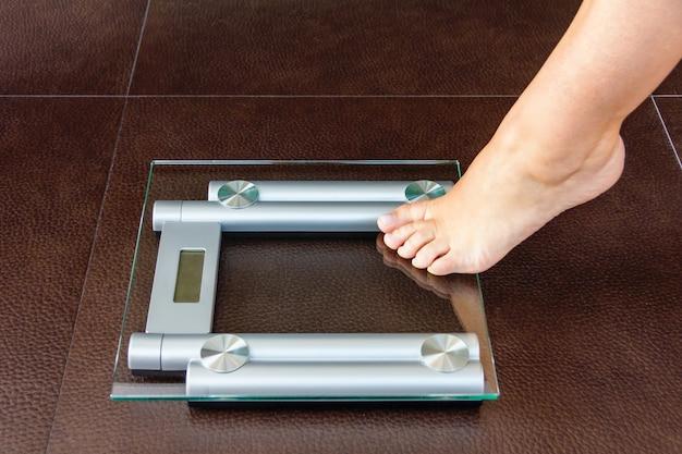 Primo piano del piede della donna che si carica sulla bilancia pesapersone. concetto di salute e peso