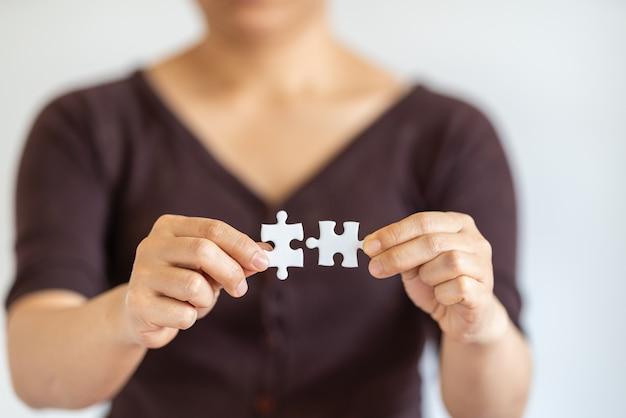Primo piano della mano della donna che tiene e collega due puzzle di carta bianca. utilizzo come soluzioni aziendali e concetto di strategia.
