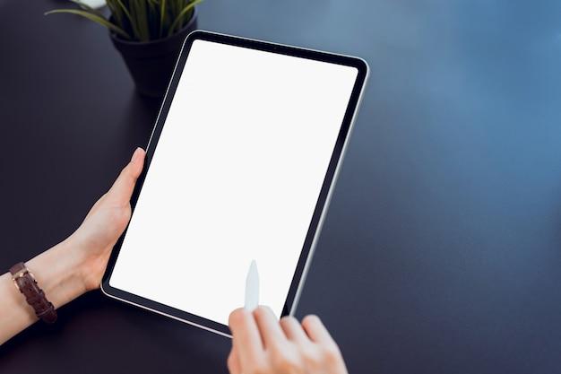Il primo piano della mano della donna che tiene la compressa digitale sulla tavola e sullo schermo è in bianco.
