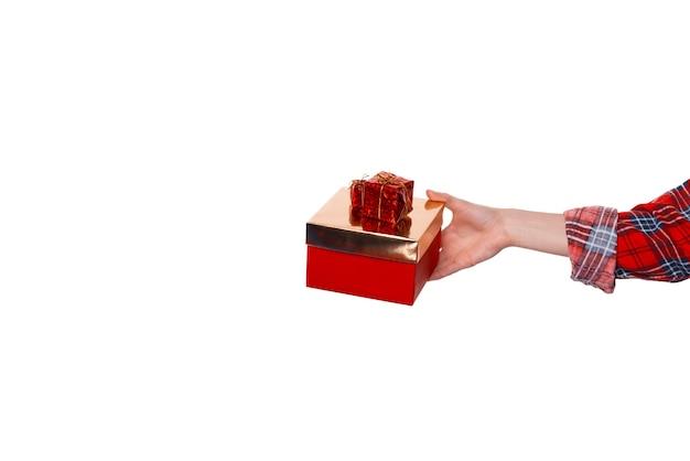 Primo piano di una mano di donna che tiene una piccola confezione regalo oro e rosso su sfondo bianco